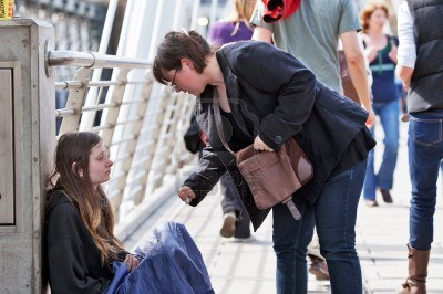10484289-london-april-2010-a-passer-by-stops-to-give-money-to-a-young-homeless-woman-on-charing-cross-bridge-