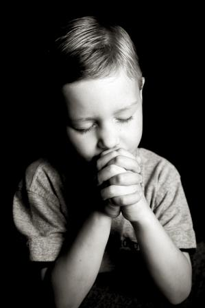 Boy praying before bedtime.
